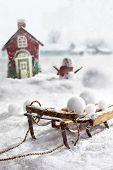 picture of sled  - Wooden sled and snowballs with snowman and wintery background - JPG
