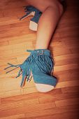 stock photo of ankle shoes  - long slim woman legs in blue ankle high heel fringe boot indoor shot on parquet retro colors - JPG