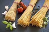 stock photo of spaghetti  - Raw spaghetti with cherry tomatoes garlic and herbs  - JPG