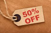 stock photo of fifties  - Fifty percent off announcement message in red text on a brown paper price tag and wrapping paper with string - JPG