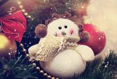 picture of ruddy-faced  - Funny snowman decoration in scarf on Christmas tree background - JPG