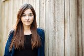 stock photo of blouse  - Closeup portrait of a young beautiful brunette woman in blue blouse and black dress with long hair against a wooden fence outdoors - JPG