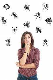 stock photo of ordinary woman  - Ordinary casual beautiful woman surrounded with zodiac signs thoughtfully looking up with questionable face expression photo conception problems with horoscope good and bad sides and features - JPG