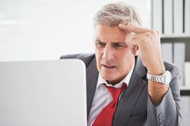 stock photo of confusing  - Confused businessman looking at his laptop in his office - JPG