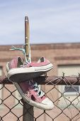 image of chain link fence  - Pair of old worn classic sneakers hang from rusty chain link fence - JPG