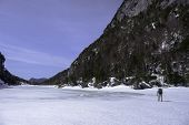 image of avalanche  - Man trecking across Avalanche Lake in the Adirondack mountains New York - JPG