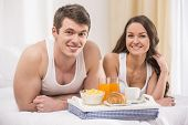 picture of bed breakfast  - Smiling young couple having breakfast in bed - JPG