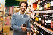 stock photo of supermarket  - Man in a supermarket choosing a wine bottle - JPG