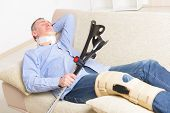 stock photo of caged  - Man with leg in neck brace - JPG