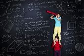 pic of frot  - Cute boy and girl learning playfully in frot of a big blackboard - JPG