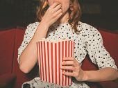 image of watching movie  - A young woman is watching a movie and is eating popcorn at the cinema - JPG