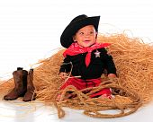 image of baby cowboy  - A happy biracial baby dressed as a cowboy sitting in a pile of hay - JPG