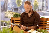 stock photo of bench  - Casual man sitting in outdoor cafe on a bench - JPG