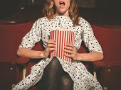 image of watching movie  - A young woman is sitting on the front row in a movie theater and is watching an exciting film while eating popcorn - JPG