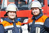 image of fire brigade  - two firefighters in uniform in front of fire engine machine and fireman team - JPG