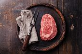 pic of meats  - Raw fresh marbled meat Black Angus Steak Ribeye and meat fork on dark background - JPG