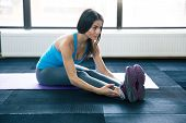 picture of yoga mat  - Young fit woman doing yoga exercises on yoga mat at gym - JPG