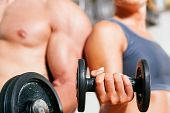 foto of muscle man  - Couple exercising with dumbbells in a gym - JPG