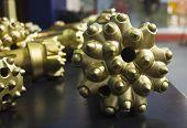 stock photo of drill bit  - New golden oil rig drill bit detail - JPG