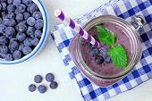stock photo of masonic  - Blueberry smoothie with mint in mason jar mug downward view on white marble - JPG