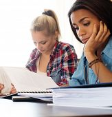 stock photo of exams  - Girls students preparing for exams in apartment interior behind table  - JPG