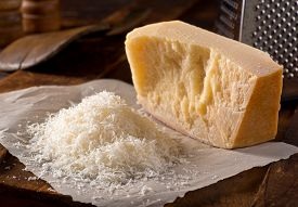 image of grating  - Freshly grated authentic parmigiano reggiano parmesan cheese - JPG