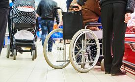 pic of wheelchair  - wheelchair bound invalid buyer in shopping center with assistant - JPG