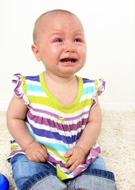 foto of teething baby  -  Ten month old baby girl crying with teething pain - JPG