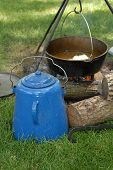 stock photo of dutch oven  - A dutch over and a coffee kettle sit by an open campfire - JPG
