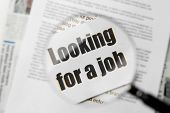Paper sheet with text LOOKING FOR A JOB through magnifier, closeup. Marketing concept poster