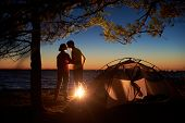 Night Camping Under Tree At Sea. Silhouettes Of Hiker Couple, Back View Of Man And Woman Stand At Ca poster