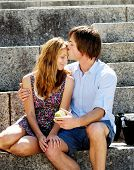 A couple traveling sit on the steps of a local landmark and kiss in the afternoon sunlight poster