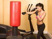 image of spandex  - Attractive woman kickboxing with red punching bag - JPG