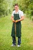 pic of young adult  - Young and smiling gardener with pitchfork - JPG