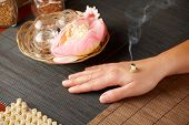 TCM Traditional Chinese Medicine. Smoking mini moxa stick, flower and natural herbs in glass jars in background. poster
