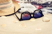 Straw Hat, Cover-up Beachwear Wrap And Sun Glasses On A Tropical Beach poster