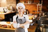 Waist Up Portrait Of Young Cook Smiling At Camera While Posing In Restaurant Kitchen, Copy Space poster