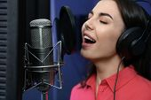 Young Singer With Microphone Recording Song In Studio poster