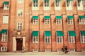 People Walking And Riding Bicycles In City With Brick Houses, Copenhagen, Denmark. poster