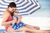 stock photo of sunburn  - Mother And Daughter Under Beach Umbrella Putting On Sun Cream - JPG