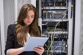 Woman using tablet pc in front of servers in data center