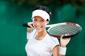 Pretty sportswoman with racket at the tennis court. Healthy lifestyle