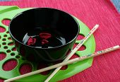 Black Bowl And The Chinese Sticks On A Red Green Background poster