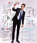 full body picture of a business man drawing or writing some graphs and diagrams with his marker, pla