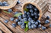 stock photo of wooden basket  - Blueberries have dropped from the basket on an old wooden table - JPG