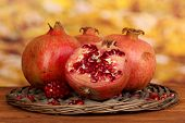 Ripe pomegranates on wicker cradle on wooden table on autum background