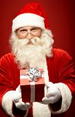 stock photo of generous  - Photo of kind Santa Claus giving xmas present and looking at camera - JPG