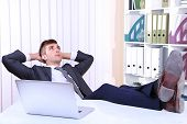 picture of table manners  - Businessman resting at his office with his shoes on table - JPG