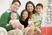 image of christmas-present  - Family With New BornSitting On SofaHolding Christmas Gift - JPG