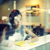 stock photo of lunch  - Cafe city lifestyle woman on phone drinking coffee texting text message on smartphone app sitting indoor in trendy urban cafe - JPG